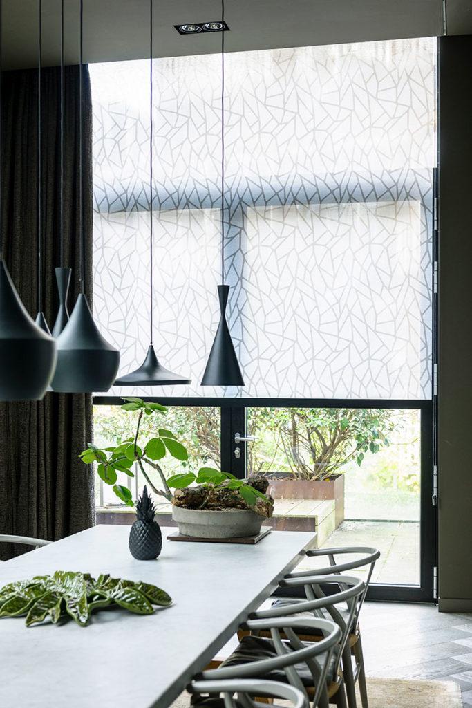 Rullegardin med mønster i kombination med mørke lange stofgardiner