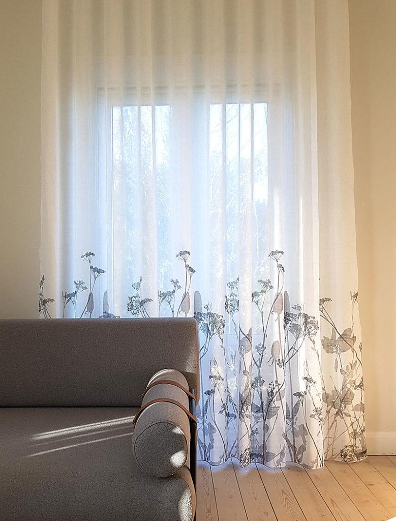 Hvide lange gardiner med mønster ved gulvet
